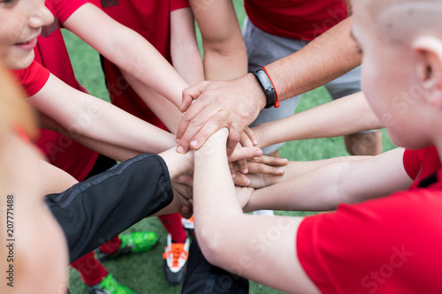 Aluminium Voetbal High angle closeup of junior football team stacking hands during motivational pep talk before match in outdoor stadium, copy space