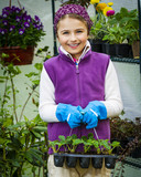 Beaitful child playing in greenhouse and care for plants. Cute girl engaged in gardening in the backyard. Spring organic growth concept. - 207778046