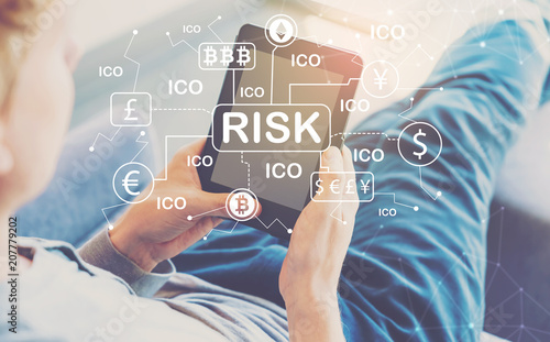 Cryptocurrency ICO Risk Theme with man using a tablet in a chair
