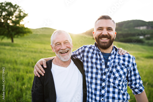 Leinwandbild Motiv A portrait of an adult hipster son with senior father in nature at sunset, arms around each other.
