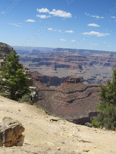 Fotobehang Beige Grand Canyon views as seen from the South Rim Trail on a sunny day with blue sky and some clouds