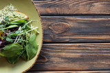 top view of vegetarian salad with spinach and sprouts on plate on wooden tabletop