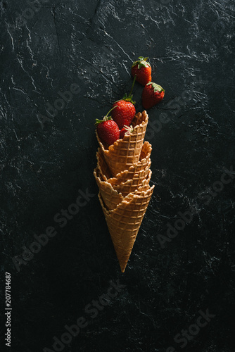 Ripe strawberries in stacked waffle cones on dark background