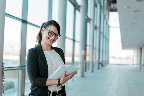 Pomyślny i zadowolony bizneswoman, trzymający notatnika, patrzeje kamerę.