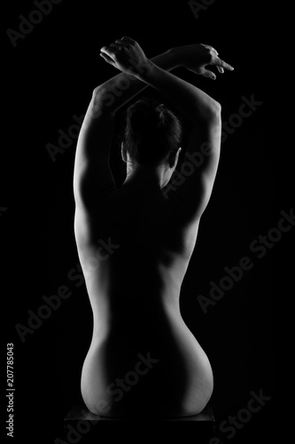 Art nude, perfect naked back, sexy woman on dark background, black and white studio shot
