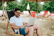 Young smiling man using laptop at the beach.