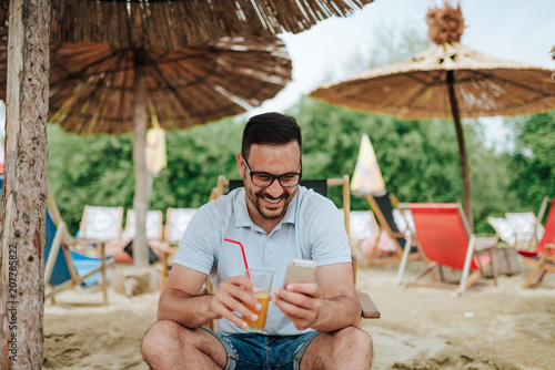 Smiling young man using smartphone while relaxing at the beach.