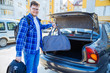 young adult man putting bag in car trunk. car travel concept