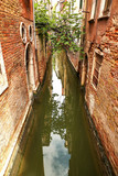 Canal between historic buildings in Venice, Italy, Europe. - 207791253