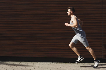 Young man running in city copy space