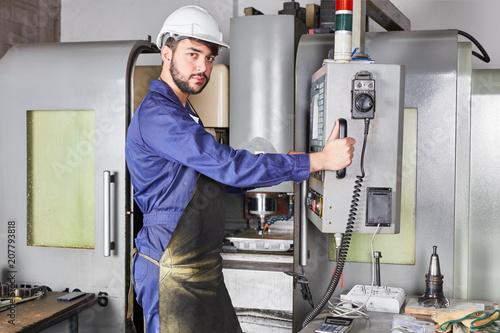 Metallarbeiter bedient CNC Werkzeugmaschine