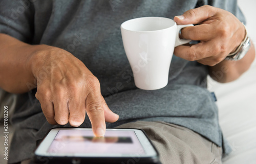 Senior male hands using a digital tablet.