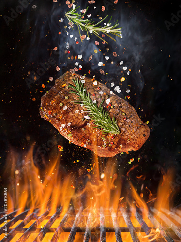 Tasty beef steak flying above cast iron grate with fire flames. - 207813863