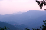 Blue hills with trees on them fading into the distance and the pink glowing sky of dusk shot in shimla. Showcases the tranquility and beauty of the place - 207818865
