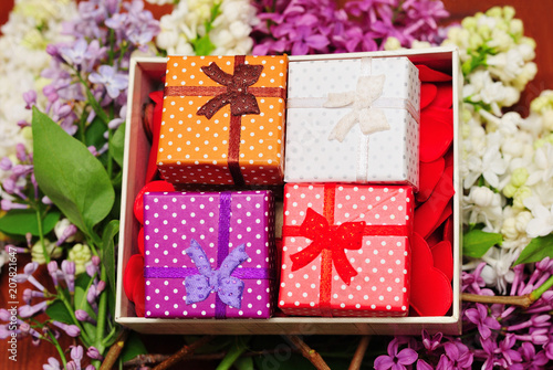 Lilacs and gift boxes on wooden background