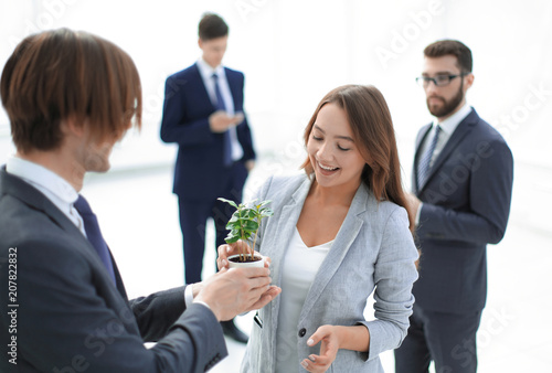 Leinwanddruck Bild businessman and businesswoman holding a pot with sprouts