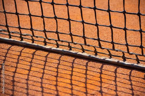Fotobehang Tennis Maschen von einem Tennisnetz werfen Schatten auf den Tennisplatz