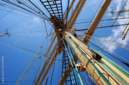 Fotobehang Schip Steel masts of a sailing ship with the lowered sails with blue sky on the background.