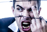 I hate social norms! Man behind a barbed wire shows a middle finger gesture as symbol of lack of freedom - 207831468