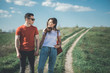 Falling in love. Full length of amorous young man and woman holding hands while strolling in nature. They are looking at each other with smile and affection. Copy space in right side