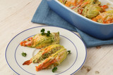 stuffed zucchini or courgette flowers baked with parmesan cheese and parsley garnish on a plate and in a casserole, blue napkin white wooden table - 207843091