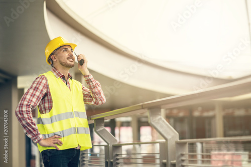 civil engineer wearing safety helmet using radio walkie talkie to command and contacting with his team