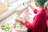 High angle portrait of creative young woman making clothes sitting at sewing machine and working in modern atelier, copy space