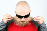 Portrait of a bald, bearded man wearing dark glasses on a light background - 207849294