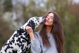 young woman licked in the face by an Dalmatian dog