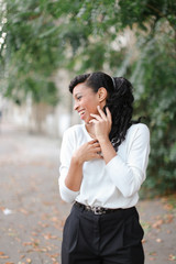 Half american nigerian girl standing in green trees background, wearing white blouse, having ponytail. Concept of nature and positive emotions.