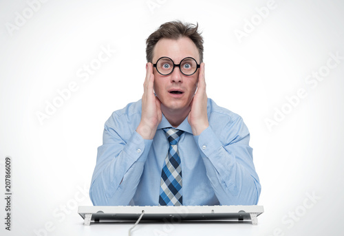 Man wearing shirt and glasses in front of a computer is very frightened
