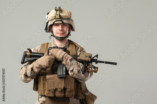 Foto Murales Soldier in camouflage holding rifle
