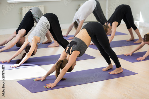 Leinwanddruck Bild Group of young sporty people practicing yoga, doing Downward facing dog exercise, adho mukha svanasana pose, yogi students working out indoor in sport club, studio. Active lifestyle, wellness concept