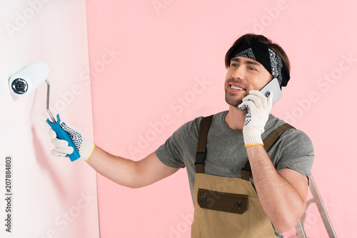 Foto Murales smiling man in protective gloves and working overall talking on smartphone and painting wall by paint roller
