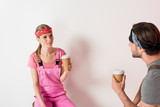 young couple in headbands and working overalls drinking coffee from paper cups - 207885005