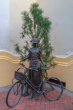 Bronze statue with a woman next to a bicycle - 207890299