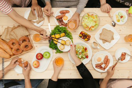 Enjoying dinner with friends.  Top view of group of people having dinner together while sitting at wooden table - 207896845