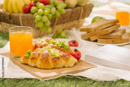 Foto Murales Sumptuous picnic spread out on a red and white checked cloth with wicker basket