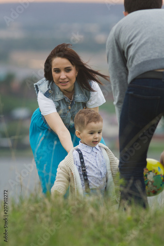 Young family with a child playing and having funat summer field