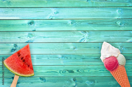 Foto Murales Watermelon popsicle and ice cream cone on blue planks background with copy space, summer concept