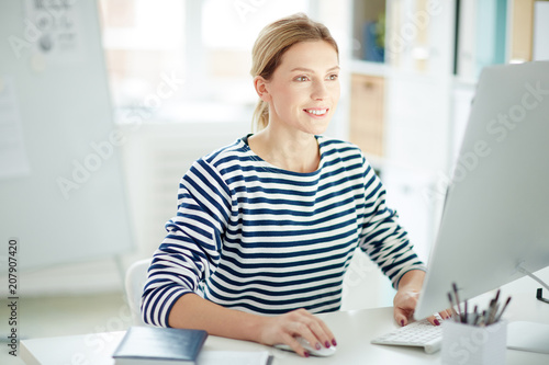 Fridge magnet Smiling manager sitting at her workplace and typing on computer
