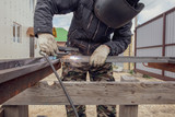 Welder welds metal at the construction site - 207910093