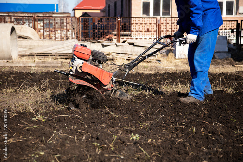Foto Murales Worker with a machine cultivator digs the soil in the garden
