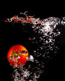 Red tomato in water on a black background - 207910695