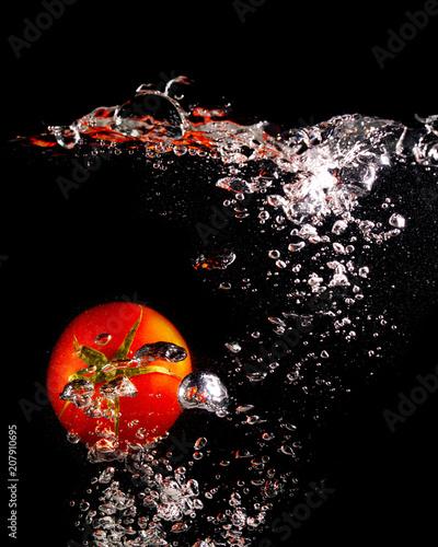 Czerwony pomidor w wodzie na czarnym tle