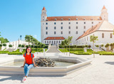 Young happy female tourist in Bratislava city near Castle or Hrad. Travel in Slovakia and Europe Union concept