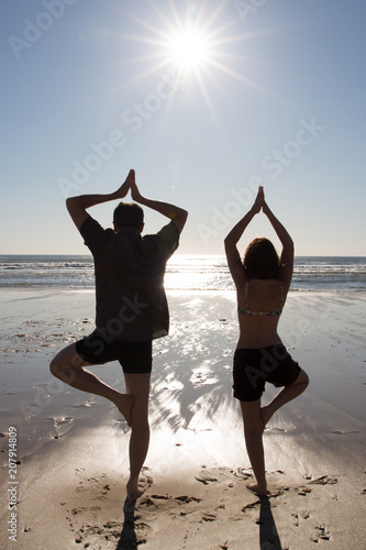 Plakat Romantic couple make yoga on the beach at colorful sunset on background