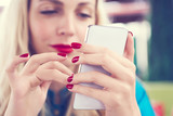 Happy Caucasian female watching on cell telephone screen while relaxing in cafe during free time - 207916296