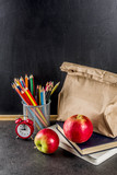 Healthy school food concept, lunch with apple, sandwich, books and alarm clock on chalkboard background copy space