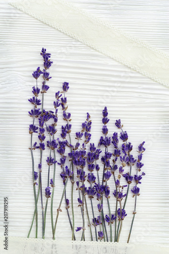 Small flowers of lavender with lace braid on white wood background with copy space. Top view. Provans style photography. © yrabota
